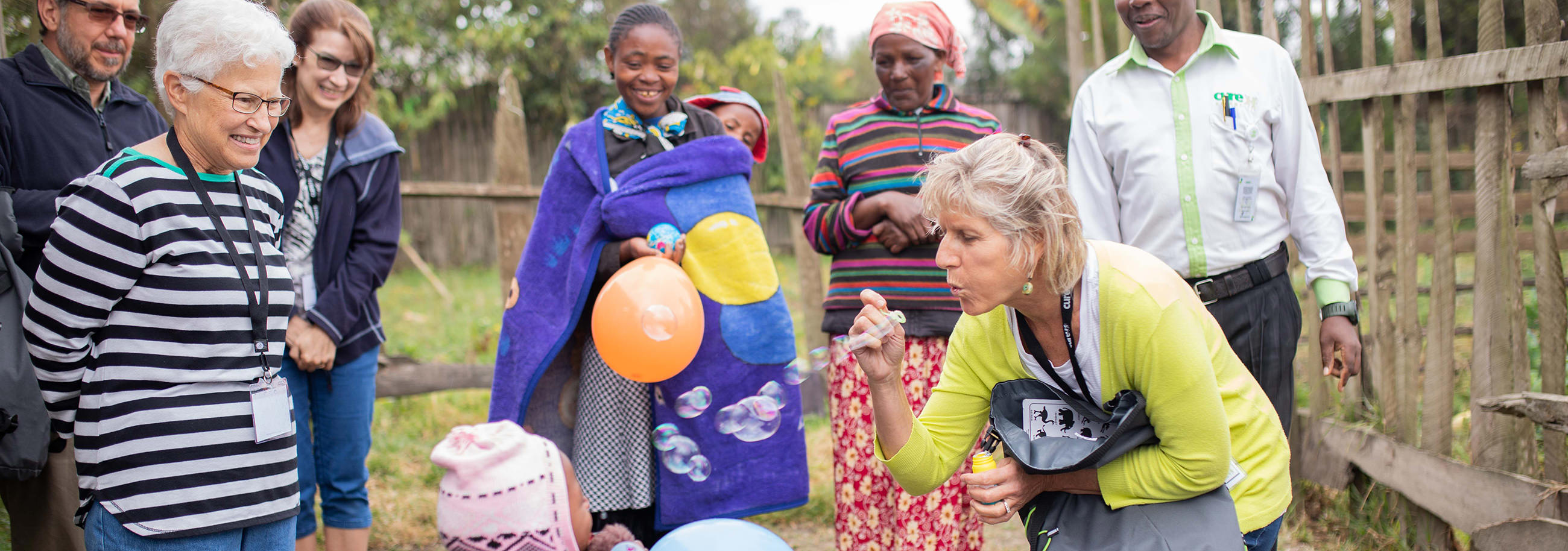 Darlene Smith, Garden Spot Village resident, and Brenda Kauffman, Garden Spot Village team member interact with a child during a Garden Spot Village Travel with Purpose trip with CURE Kenya.