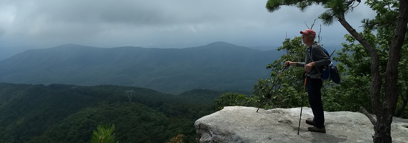 Bruce Munshower takes a moment to rest as he enjoys the beautiful view at McAfee Knob, on Catawba Mountain near Roanoke, Virginia.