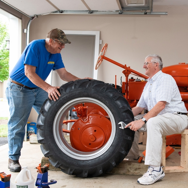 Dale Hostetter and Ed Blakeslee work on Ed's tractor in Dale's garage.