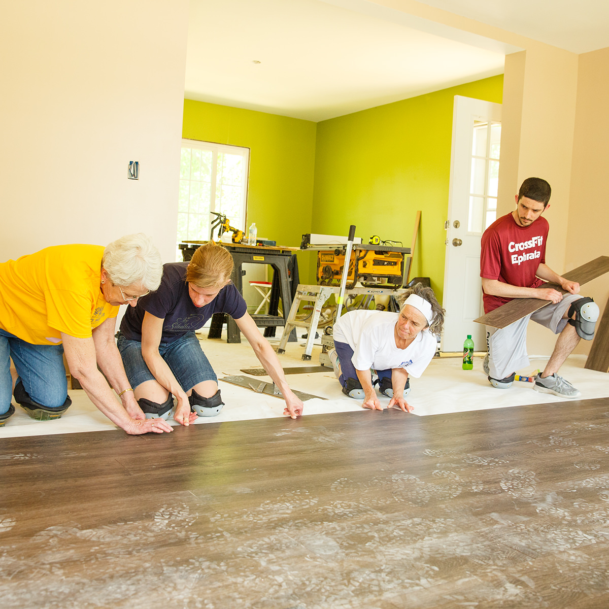 Team members and resident from Garden Spot Village helping to install flooring in house on Travel With Purpose Mission Trip with Garden Spot Village.