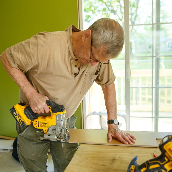 Lloyd Ziegler cutting a piece of flooring with a saw