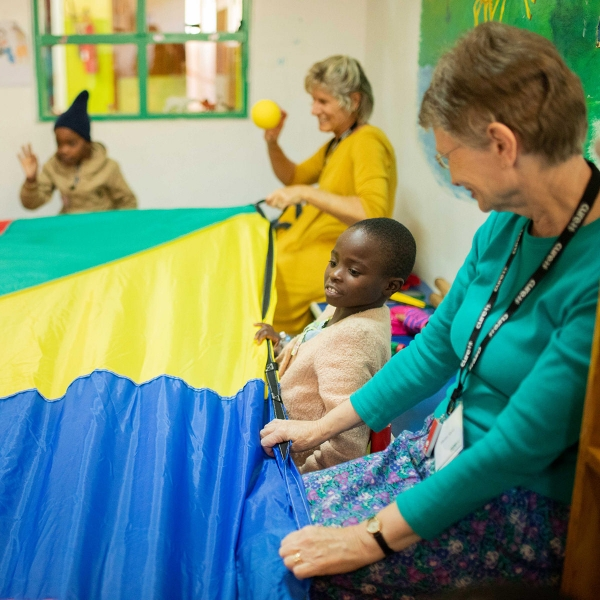 Marion Sacks and Brenda Kauffman use a parachute to play with children at the CURE Kenya Hospital in Kijabe, Kenya.