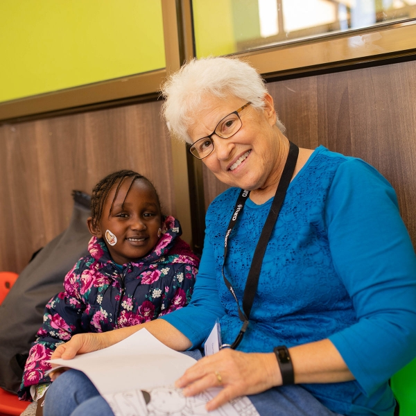 Darlene Smith, a Garden Spot Village resident, reads a book to a child at the CURE Kenya hospital in Kijabe, Kenya.