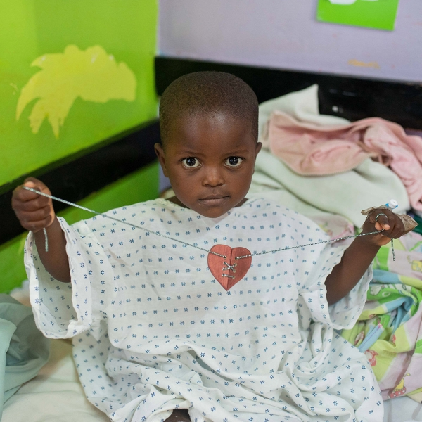A child at the CURE Kenya hospital in Kijabe, Kenya, holds a mended heart, given to him by the Garden Spot Village Travel with Purpose in September 2018.